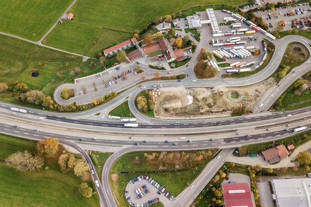 Top down aerial view of freeway interstate road with moving traffic cars in rural area.