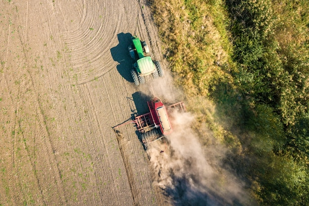 Top down aerial view of green tractor cultivating ground and seeding a dry field