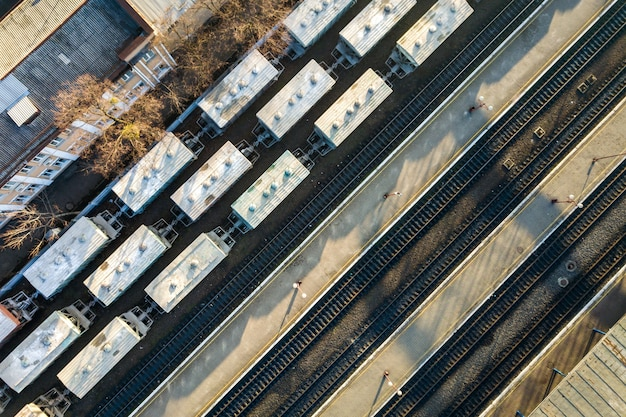Top down aerial view of many cargo train cars on railway tracks.