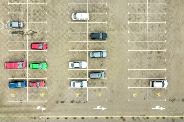 Top down aerial view of many cars on a parking lot of supermarket or on sale car dealer market.