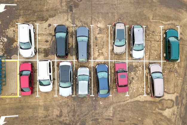 Top down aerial view of many cars on a parking lot of supermarket or on sale car dealer market