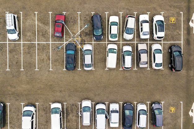 Top down aerial view of many cars on a parking lot of supermarket