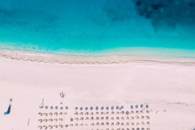청록색 바다에 우산과 선베드가있는 깨끗한 해변의 하향식 공중 뷰. 그리스.