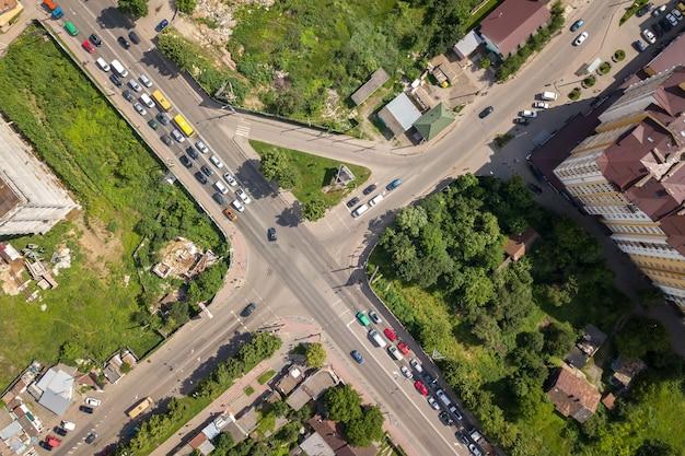 移動中の車の交通量のあるにぎやかな通りの交差点の空中写真を上から見下ろします。