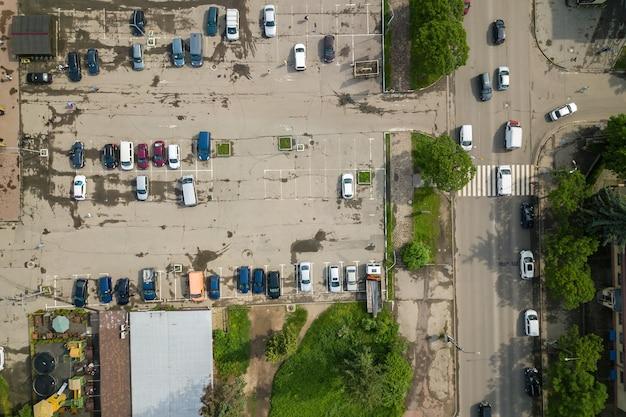 Вид сверху вниз на оживленную улицу с движущимися автомобилями и большую парковку со множеством припаркованных автомобилей.