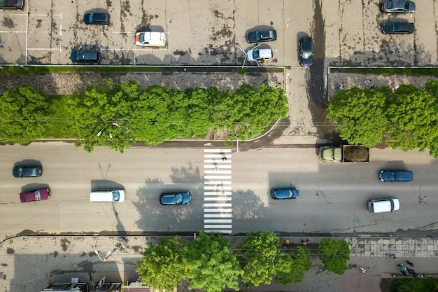 Вид сверху вниз с высоты птичьего полета на оживленную улицу с движущимся автомобильным движением и пешеходный переход на зебровой дороге.
