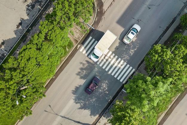移動する車の交通とゼブラ道路の横断歩道があるにぎやかな通りの空中写真を上から見下ろします。