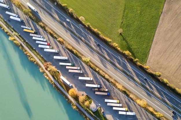 빠르게 움직이는 트래픽과 주차 된 트럭 트럭이있는 주차장이있는 고속도로 주간 도로의 공중보기.