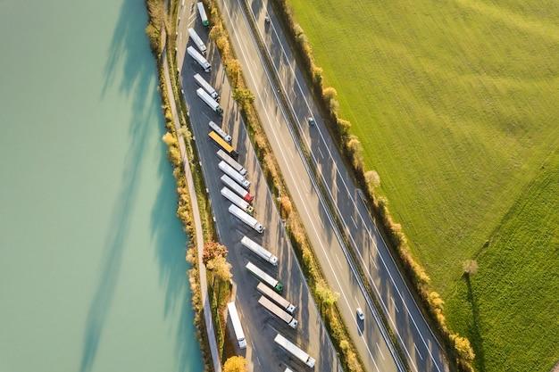 高速で移動する交通量のある高速道路の州間道路と駐車した大型トラックの駐車場の空中写真。