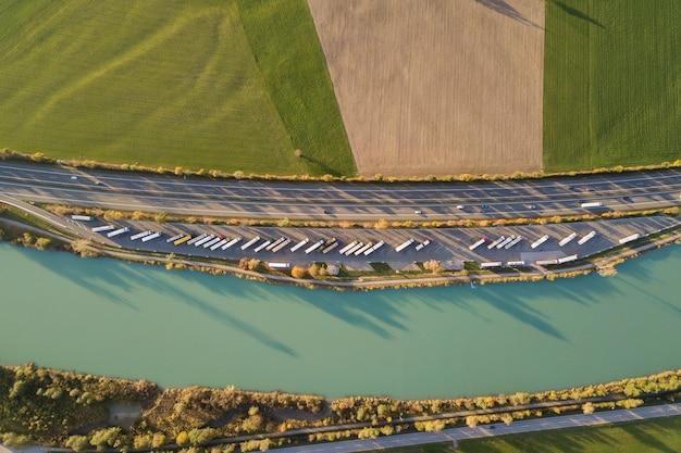 高速で移動する交通のある高速道路の州間道路と駐車したトラックの駐車場を上から見下ろした図。