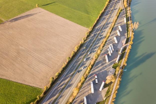 高速移動する交通のある高速道路の州間道路と駐車されたトラックの駐車場の空撮を上から見下ろしてください。