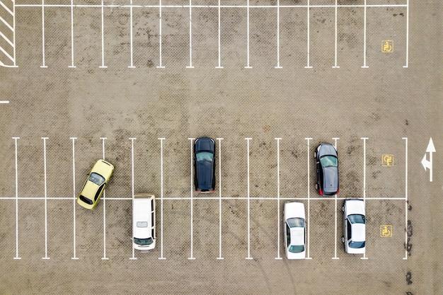 スーパーマーケットの駐車場や販売中の自動車ディーラー市場にある多くの車の空中写真を上から見た図。