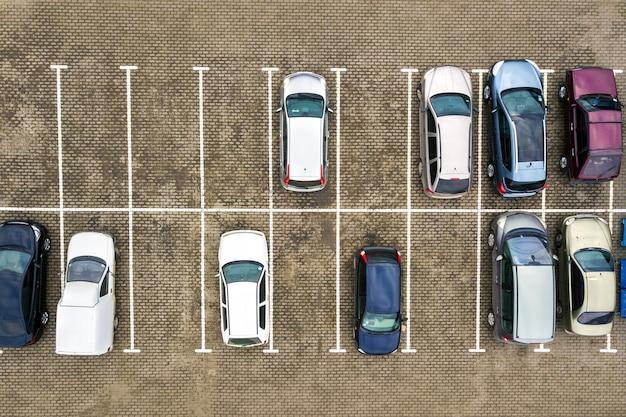 スーパーマーケットの駐車場や販売中の自動車ディーラー市場にある多くの車の空中写真を上から見下ろします。
