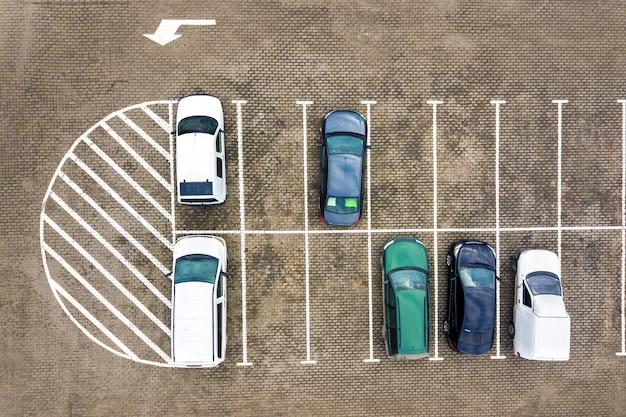 Вид сверху вниз на множество автомобилей на стоянке супермаркета или на рынке дилеров по продаже автомобилей.