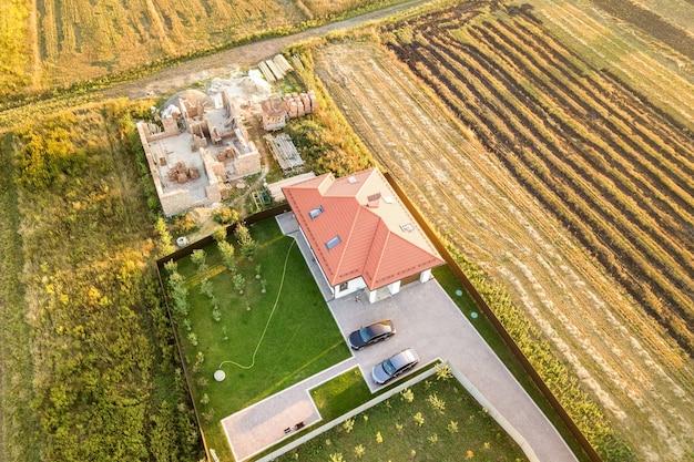 콘크리트 기초와 벽돌 벽으로 건설 중인 주택과 붉은 기와 지붕으로 마감된 다른 주택 등 2개의 개인 주택을 위에서 내려다 본 모습입니다.