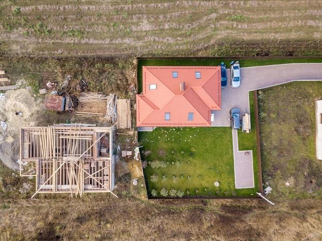 2つの民家の空撮を上から見下ろします。1つは木製の屋根枠で建設中、もう1つは赤い瓦屋根で仕上げられています。
