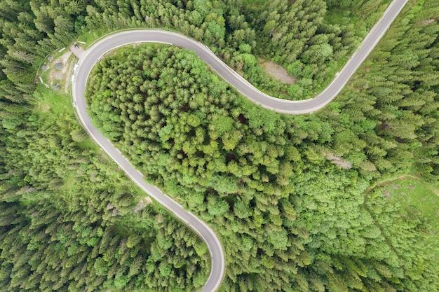 緑の山トウヒの森の曲がりくねった林道の空撮を上から見下ろします。
