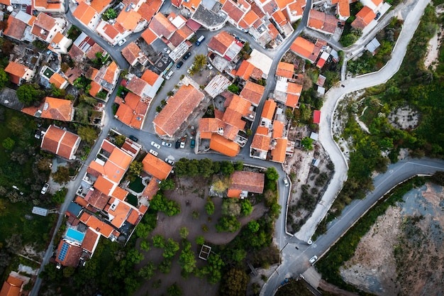Top down aerial view on red roofs of houses in a small village.