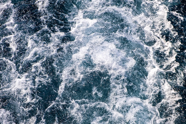 Top down aerial view of sea water surface. white foam waves texture as natural background.
