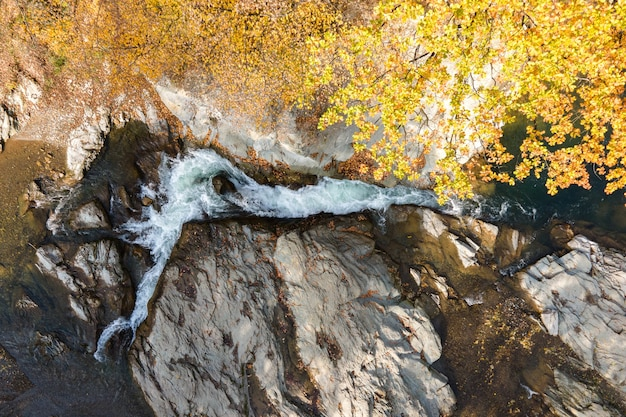 Top down aerial view of small mountain stream with fast moving clear water between rocky stones