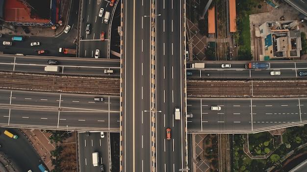 Сверху вниз перекрестное движение по шоссе с легковыми автомобилями, грузовиками с антенной. городской транспорт на мостовой дороге в