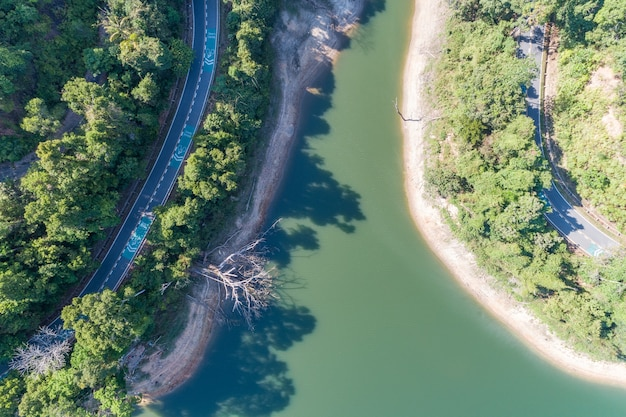 Top down from drone aerial view of rainforest with asphalt road around the dam and shared land beware bike sign on road.