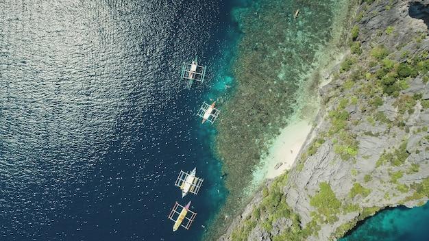 바위 바다 해안 조감도에서 전통적인 보트의 하향식. 태양에서 배와 장엄한 바다 경치