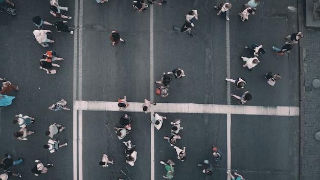 Top down pedestrians crosswalk road aerial people cross street cityscape crossroad men women walking