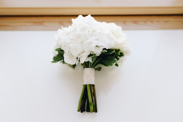 A top-down picture of a hydrangea wedding bouquet on a window-sill