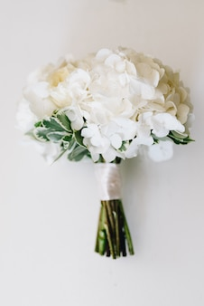 A top-down picture of minimalistic wedding bouquet of white hydrangea