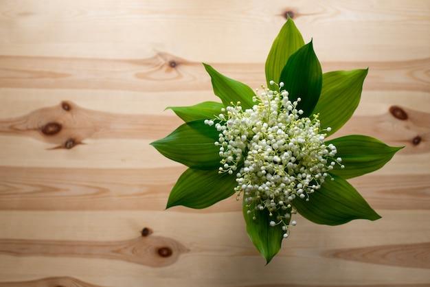 古い木製のテーブルの上の谷のユリの美しい花束のトップダウンショット