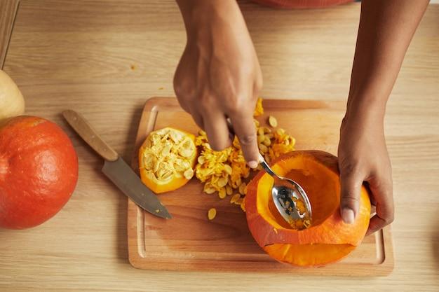 スプーンを使用して小さな熟したカボチャから種子と繊維をすくう女性の手のトップダウンショット
