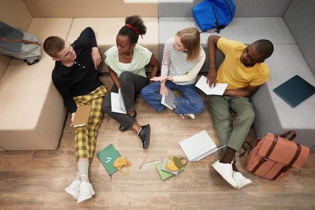 Вид сверху вниз на разнообразную группу молодых студентов, обучающихся вместе, сидя на полу в колледже ...