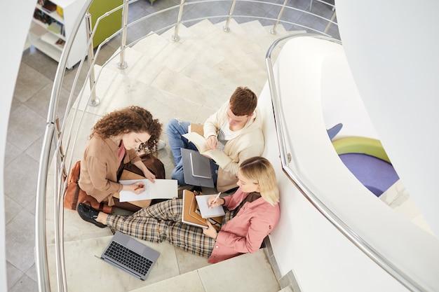 Вид сверху вниз на группу студентов, сидящих на лестнице в колледже и вместе работающих над домашним заданием,
