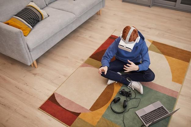 Вид сверху на рыжего подростка, играющего в видеоигры в vr, сидя на полу на ковре с рисунком, скопируйте пространство