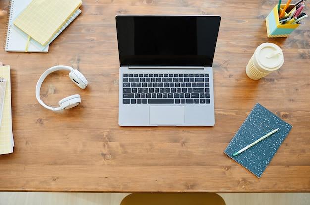 Вид сверху на стол для подростков с открытым ноутбуком на деревянном столе и аксессуарами, копией пространства