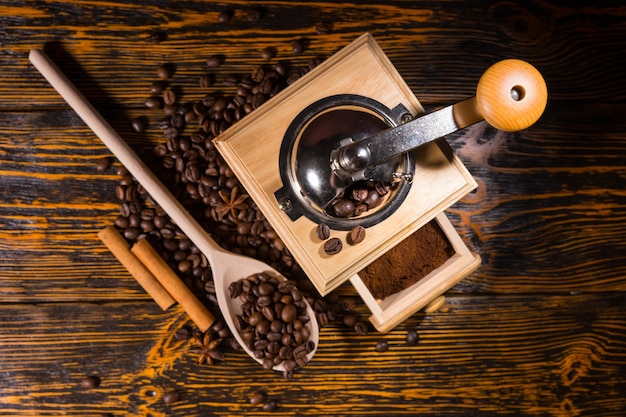 Top down view on coffee grinder full of finished grounds in drawer, wooden spoon and two cinnamon sticks surrounded by beans on table