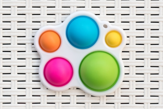 Top down view on a colorful symple dimple fidget toy, an ergonomic tactile stress reliever through decompression of the silicone buttons displayed on white cane or rattan