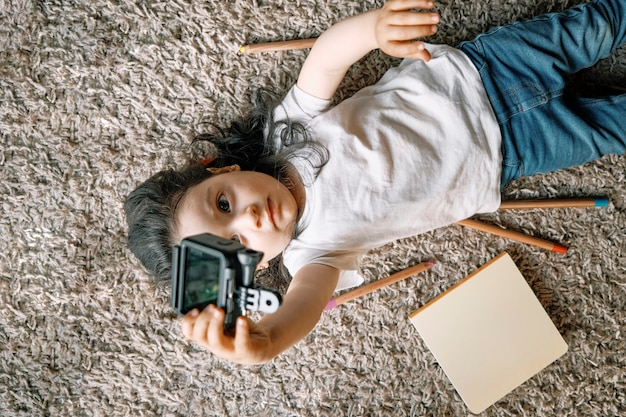 Top down view of a little girl playing on the carpet with a toy camera holding a selfie with notebooks and colored pencils around