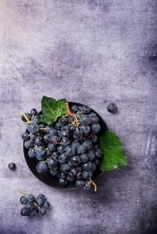 Вид сверху вниз на черный виноград с зелеными листьями на темном столе, скопируйте место для текста