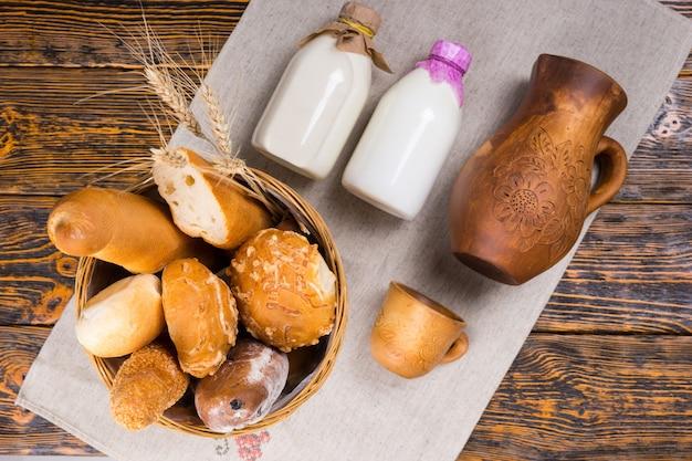 古い木製のテーブルの上に白い紙の上の牛乳瓶、ピッチャー、カップの横にあるパンでいっぱいのパンバスケットのトップダウンビュー