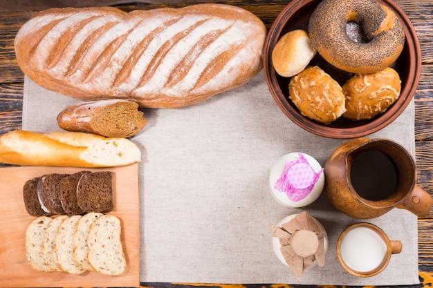 木製のテーブルの上の布の上のパン、スライス、ロールパン、ベーグル、牛乳瓶のトップダウンビュー