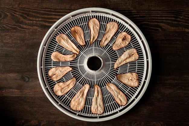 暗い木製のキッチンテーブルの中央にあるフルーツ乾燥機の丸いトレイに乾燥した梨のスライスの上面図