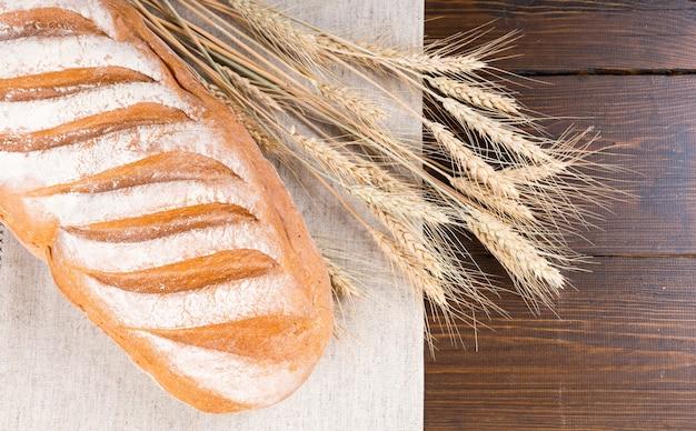 暗い木製のテーブルの上の乾燥小麦の茎の横にある紙に小麦粉の薄いコーティングを施した大きな白パンのパンの上面図