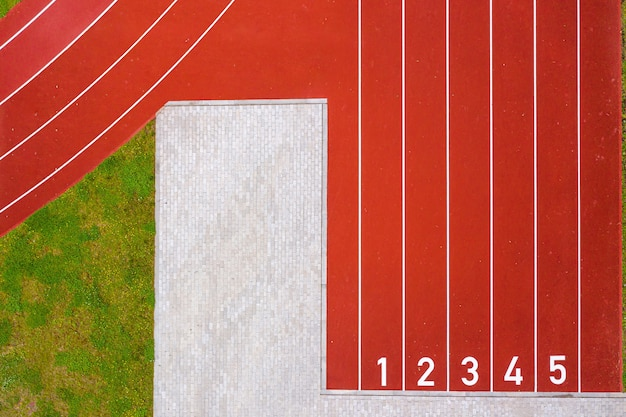 Вид сверху на красные беговые дорожки, начинающиеся с цифр и лужайку с зеленой травой, красную беговую дорожку на стадионе, инфраструктуру для занятий спортом