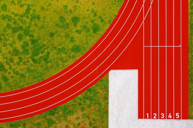 赤いランニングトラックのトップダウンビューは、数字と緑の芝生の芝生から始まり、スタジアムの赤いランニングトラック、スポーツ活動のインフラストラクチャ