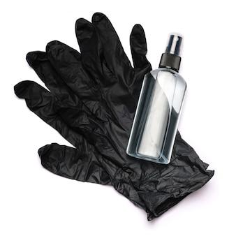 Сверху вниз вид дезинфицирующего средства над защитной резиновой латексной одноразовой перчаткой.