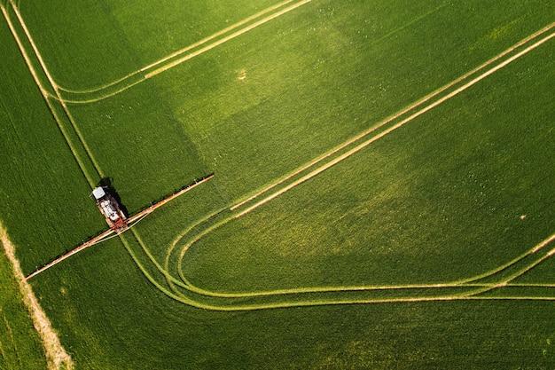 넓은 녹색 들판에 화학 물질을 뿌리는 트랙터의 하향식 보기