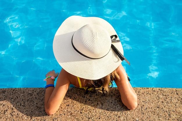 夏の晴れた日に、澄んだ青い水のプールで休んでいる黄色い麦わら帽子をかぶった若い女性のトップダウンビュー。