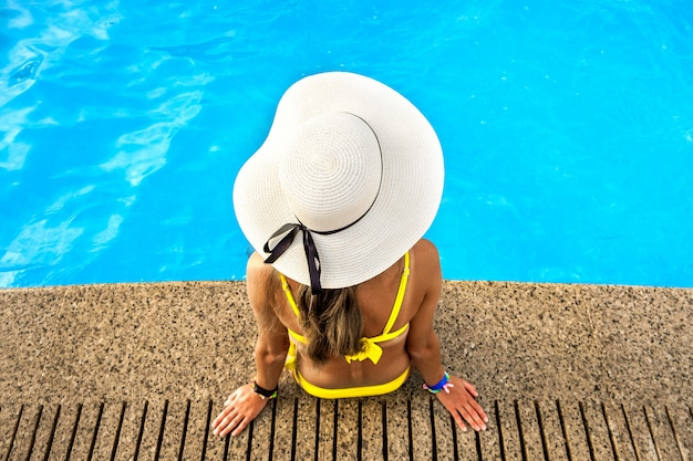 夏の晴れた日に澄んだ青い水とスイミングプールのそばで休んでいる黄色の麦わら帽子を着た若い女性のトップダウンビュー。